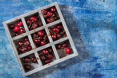 Wooden box with sweet cherry on blue background. Royalty Free Stock Image