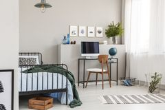 Wooden box under single metal bed with blue sheets and green blanket in trendy kid`s room with workspace royalty free stock photos