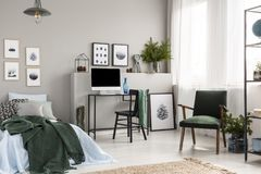 Wooden box under single metal bed with blue sheets and green blanket in trendy kid`s room with workspace