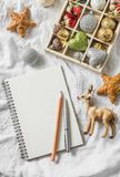 Wooden box of vintage christmas decorations and clean notepad on the light background, top view. Royalty Free Stock Images