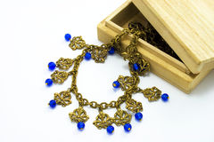 Wooden box with vintage necklace. Wooden box, vintage gold necklace with blue beads inside Stock Photos
