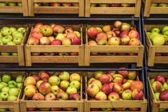 Wooden boxes of apples in the supermarket. Organic apples in wooden boxes in the supermarket are sorted by varieties Royalty Free Stock Images