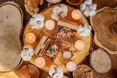 Wooden boxes with rings. Two beautiful handmade wooden boxes with rings on wooden background with candles and cotton flowers Royalty Free Stock Photos