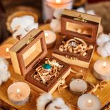 Wooden boxes with rings. Two beautiful handmade wooden boxes with rings on wooden background with candles and cotton flowers Stock Photos