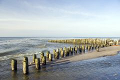 Wooden breakwater on beach. Scenic view of wooden breakwater on sandy beach with sea in background Stock Photography