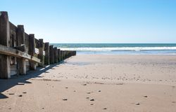 Wooden breakwater on a calm beach stock images