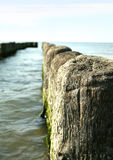 Wooden breakwater in ocean Stock Photos