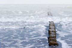 Wooden breakwater and waves, stormy sea weather Royalty Free Stock Photo