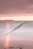 Wooden breakwater on wavy Baltic Sea.  Pink horizon with first hot sun rays. Stock Images