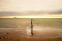 Wooden breakwater on wavy Baltic Sea.  Pink horizon with first hot sun rays. Royalty Free Stock Photos