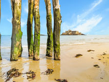 Wooden breakwaters in low tide and Fort National Royalty Free Stock Photo