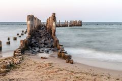 Wooden breakwaters on the sea shore.  stock photos