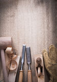 Wooden bricks hammer curled up scobs planer firmer chisels leath. Er gloves on wood background construction concept Stock Photos