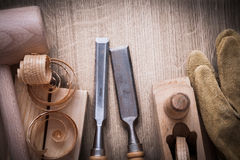 Wooden bricks mallet curled up shavings planer firmer chisels le. Ather gloves on wood background construction concept Stock Image