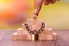 Wooden bricks tied with a chain. Concept: stability protection royalty free stock photography