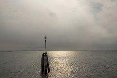 Wooden bricole with public lighting in the sea on the way from Chioggia to Venice, Italy stock photo
