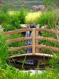 Wooden Bridge. Curved wooden bridge over a stream and waterfall Royalty Free Stock Photos