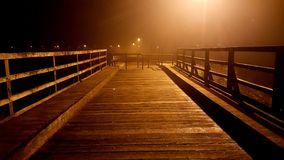 Wooden bridge access blocked with massive handrails at foggy night. Wooden bridge access blocked with massive metal handrails at foggy night with bright city Stock Photography