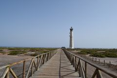 Faro de Morro Jable Lighthouse, Fuerteventura. A wooden bridge across the marsh, and Faro de Morro Jable Lighthouse on the coast in Morro Jable, south of royalty free stock photos