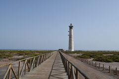 Faro de Morro Jable Lighthouse, Fuerteventura. A wooden bridge across the marsh, and Faro de Morro Jable Lighthouse on the coast in Morro Jable, south of stock photos