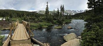Wooden bridge across mountain river Royalty Free Stock Image