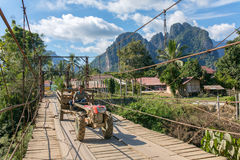 Wooden bridge across Nam Song River in Vang Vieng village, Laos. Vang Vieng, Laos - January 19, 2017: Wooden bridge across Nam Song River in Vang Vieng village stock photo