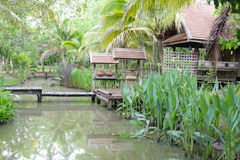 Wooden bridge across the pond and thailand traditional house Stock Photography