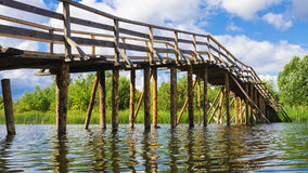 Wooden bridge across the river Royalty Free Stock Photo