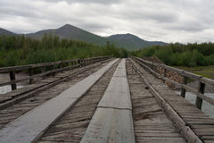 Wooden bridge across the river. Royalty Free Stock Image