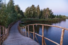 Wooden bridge across the river. Wooden footbridge across stream in the forest Stock Photo