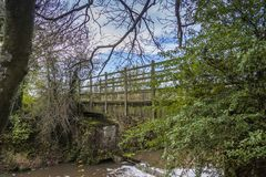 Wooden bridge across Rother river. Shadowed by green trees and with blue sky Stock Image