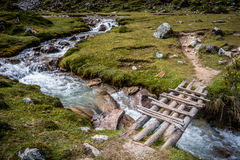 Wooden bridge across running river in the countryside Royalty Free Stock Photography