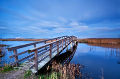 Wooden bridge for bicycles over river in dusk Royalty Free Stock Images
