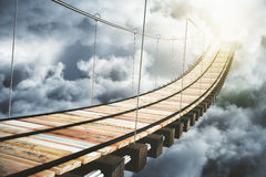 Wooden bridge in the clouds going to sunlight Royalty Free Stock Photo