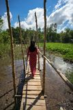 Wooden bridge connecting Champa village to river in Mekong delta, Vietnam. Champa girl walking on bridge.  Stock Photography