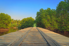 Wooden bridge in the countryside crossing the river at sunset. Stock Photo