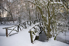 Wooden bridge covered with snow. In a forrest Stock Images