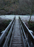 Wooden bridge crossing a river Royalty Free Stock Photo