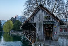 A wooden bridge crossing the river Aare in Thun with the Jungfrau and Eiger mountains in the background early in the morning - 1. A wooden bridge crossing the stock photo