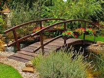 Wooden bridge in the garden. Wooden bridge in garden with ornamental trees and flowers Royalty Free Stock Photos