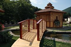 Wooden bridge and gazebo. A summerhouse in a domestic garden in summer, with small bridge over the artificial lake Stock Images