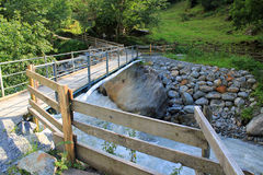 Wooden bridge for hikers over river, waterfall in the mountains, Switzerland. Wooden bridge for hikers over river, waterfall in the mountains of the royalty free stock images