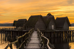 Wooden bridge and houses suspended over lake water Royalty Free Stock Photo