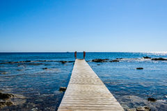 Wooden bridge juts out into the expanse of the sea Stock Photo