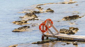 Wooden bridge juts out into the expanse of the sea Stock Images