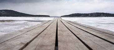 Wooden bridge and lake, covered with ice. Dramatic plot. lake covered with ice and wooden bridge Royalty Free Stock Image
