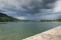 Wooden bridge on the lake in a mountain valley, storm clouds. Royalty Free Stock Images