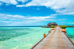 Wooden bridge leading to an exotic bungalow on the background of azure water, maldives royalty free stock photos