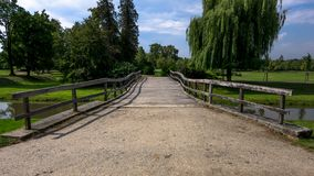 Wooden bridge leading to the park. Front view. Noon aproaching, stream and trees visible royalty free stock photos