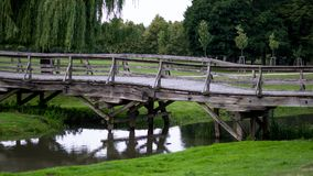 Wooden bridge leading to the park side view. Wooden bridge made of planks leading to the park above the stream, the side view royalty free stock images